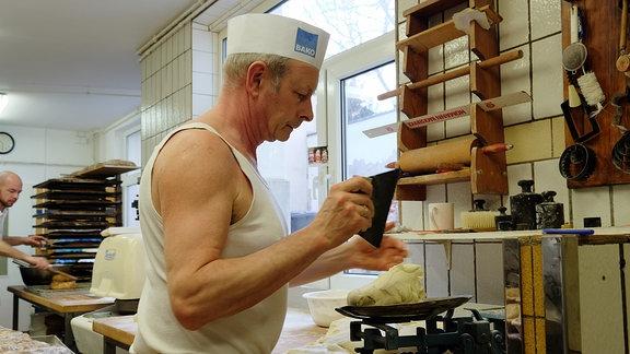 Ein Bäcker wiegt Teig auf einer alten Metallwage ab.