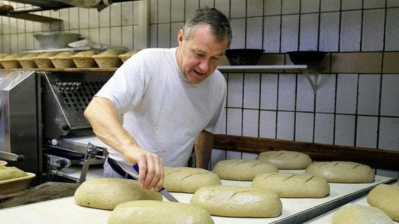 Ein Mann schneidet mit einem kleinen Messer Brotteiglinge ein bevor sie in den Ofen geschoben werden.