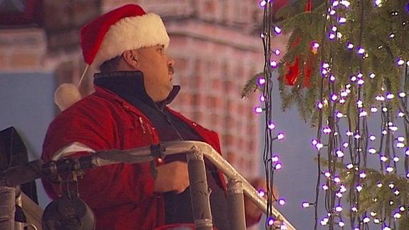 Ein Mann schmückt einen großen Weihnachtsbaum