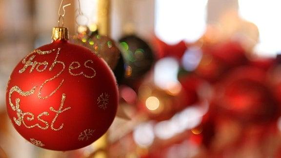 """""""Frohes Fest"""" steht auf einer roten Weihnachtskugel"""
