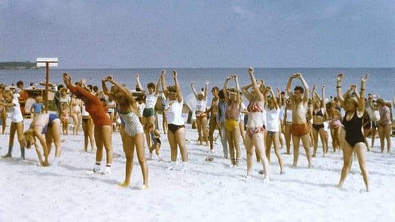 Menschen bei der Gymnastik an einem Strand
