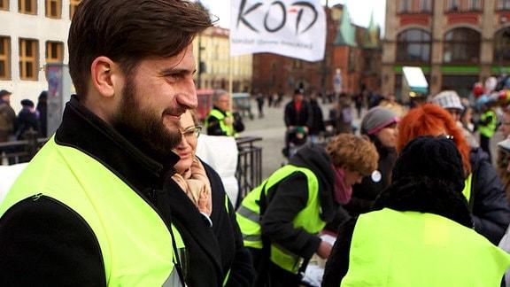 Menschen mit gelben Warnwesten auf der Straße. Im Vordergrund eine junger Mann mit Vollbart.