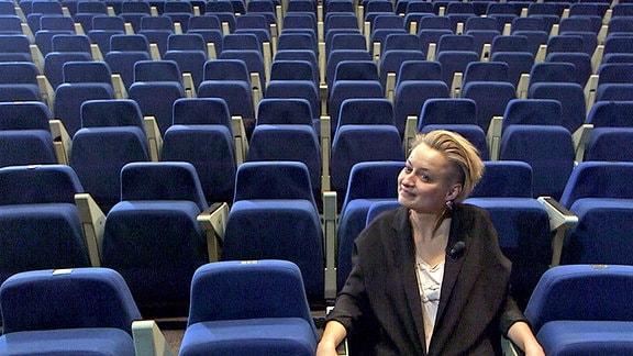 Zuschauerraum eines Theaters. Man blickt auf Reihe von leeren blauen Sesseln. Auf einem in der ersten Reihe sitzt eine junge Frau.