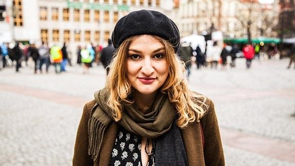 Eine junge Frau mit schulterlangem Haar und Baskenmütze auf einem Marktplatz.