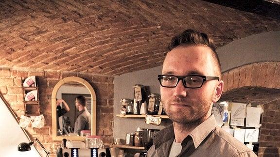 Junger Mann mit Fünftage-Bart und Brille hinter dem Tresen eines Cafés.