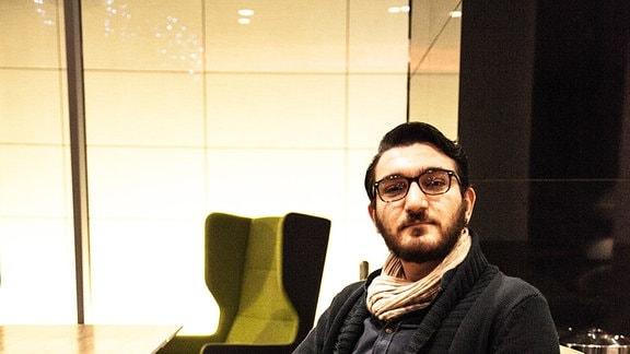 Junger Mann mit kurzem schwarzen Vollbart und Brille auf einem Sofa.