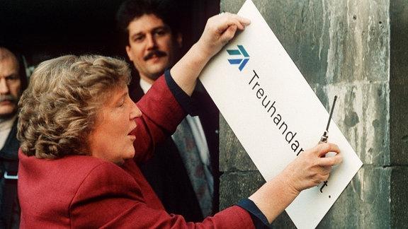 Birgit Breuel entfernt am 30.12.1994 eigenhändig mit einem Schraubenzieher das Firmenschild am Eingang der Treuhandanstalt in Berlin