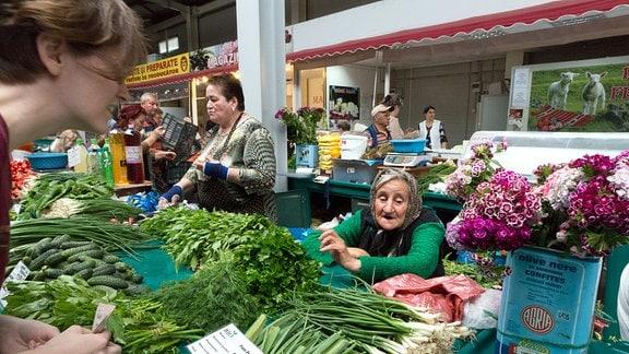 Junge Frau kauft auf einem Gemüsemarkt in Bukarest ein