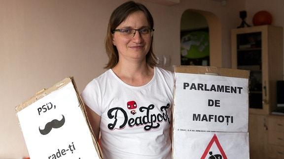 Junge Frau zeigt Protestplakate in Bukarest