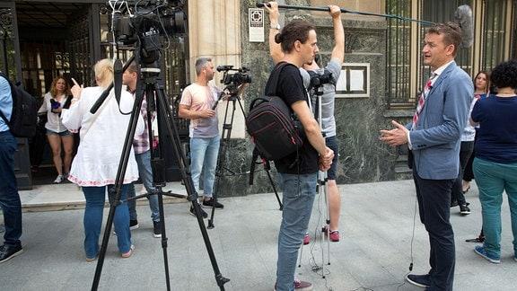 Journalisten befragen Rechtskläger auf Straße in Bukarest