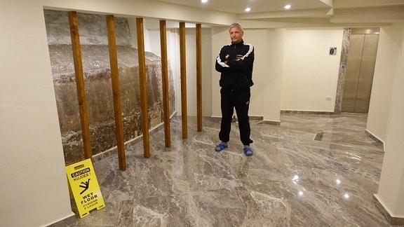 Kujtim Roçi und neben der Außenwand seines Bunkers in der Empfangshalle des Hotels Elesio.