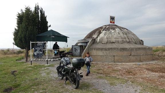 Außenasicht des Bunkers von Keq Marku nahe der Ortschaft Koplik in Nordalbanien. Im Vordergrund sein Sohn Johnny.