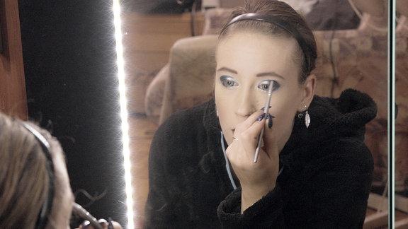 Eine junge Frau sitzt vor einem Spiegel und schminkt sich.