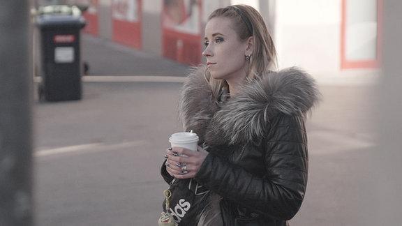 Ein junge Frau schaut verträumt und hält einen Kaffee in der Hand.