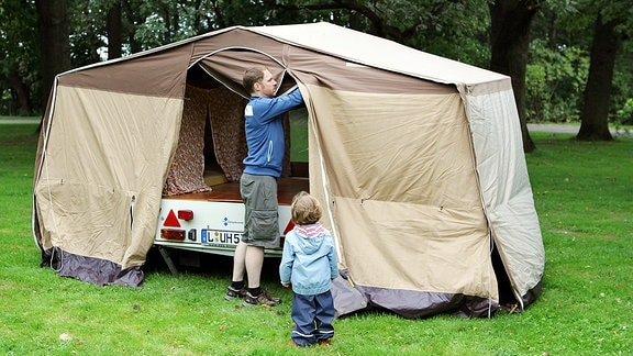 Ein Mann baut mit seiner Tochter einen Zeltanhänger Camptourist CT-7 in Leipzig auf.