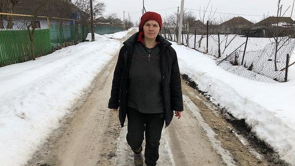 Eine Frau auf einer winterlichen Straße
