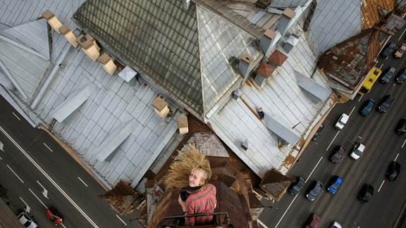 junge Frau mit wehenden blonden Haaren und Kamera in der Hand guckt aus der Luke eines Schornsteins