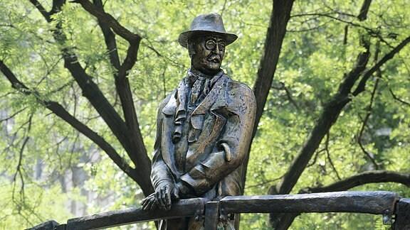 Eine lebensgroßen Bronzestatur in Gestalt eines Mannes mit Hut, steht an einem Brückengeländer.