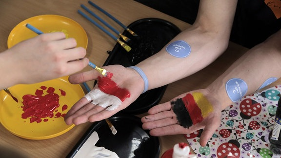 Jugendliche malen sich deutsche und polnische Fahne auf die Handfläche