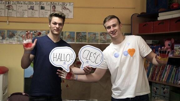 """Zwei Jugendliche zeigen Sprechblasen aus Pappe mit dem deutschen """"Hallo!"""" und dem polnischen """"Cześć"""""""