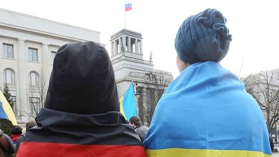 zwei Menschen je in eine deutsche und ukrainische Fahne gehüllt