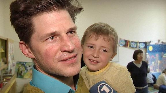 Ein Vater mit Sohn auf dem Arm