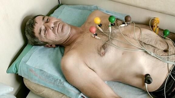 Jewgeni aus Son unterzieht sich in einem Behandlungsabteil der EKG-Diagnostik.
