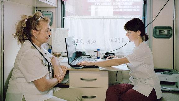 Die Allgemeinmedizinerin Ljudmila Michailowna Danilowa (links) und ihre Assistentin werten in dem kleinen Behandlungsabteil ihre Diagnosen aus.