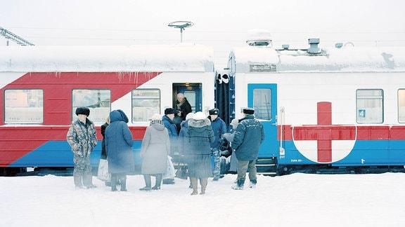 Patienten warten vor dem Registrierungswaggon am Beginn des Zuges auf Einlass.