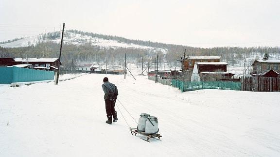 """Ein Mann holt Wasser aus einer der Pumpen im Dorf€"""" nur wenige Häuser in Son verfüˆgen üˆber flieߟendes Wasser."""