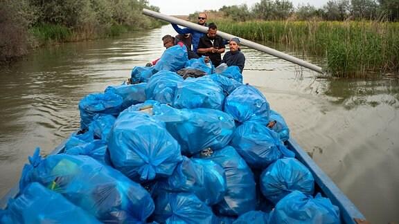 Eine große Anzahl von Müllsäcken werden per Boot zur Müll-Entsorgung gebracht.