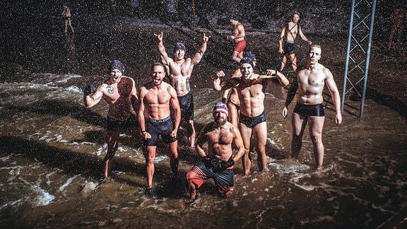Eisbaden in der Danziger Bucht - eine Männergruppe geht im Dunkeln bei Schneetreiben ins Wasser der Ostsee.