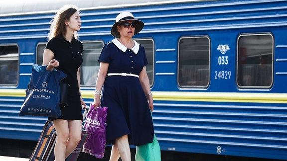 Zwei Frauen mit Gepäck vor einem Zug