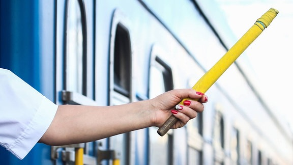 Eine Frau hält einen gelben Stab aus einem Zug.