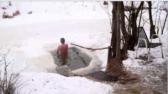 Nackter Mann steigt in ein Eisloch