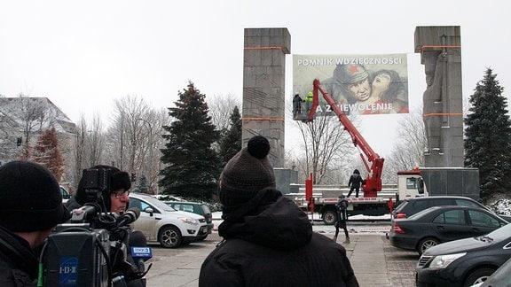 """An das Denkmal zur Befreiung der Erde von Ermland-Masuren wird ein Banner angebracht mit der Aufschrift: """"Zum Dank für die Unterdrückung"""""""