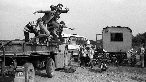 Feierabend - Jugendliche springen von einem Hänger nach ihrem Einsatz während der Kartoffelernte der LPG Dahme
