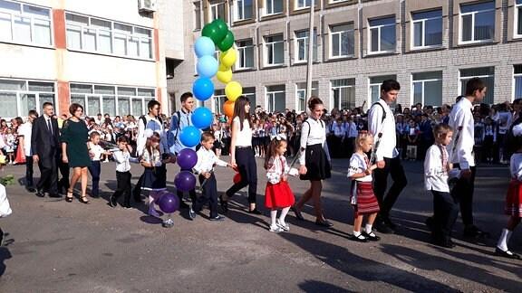 Schüler laufen durch ein Tor aus Luftballons.