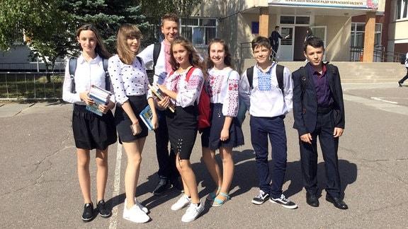 Gruppe von Mädchen und Jungen vor einem Schulgebäude.
