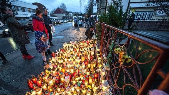 Menschen haben vor einem Haus Kerzen angezündet