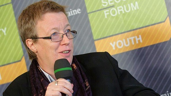 Frau Brille hält Mikrofon
