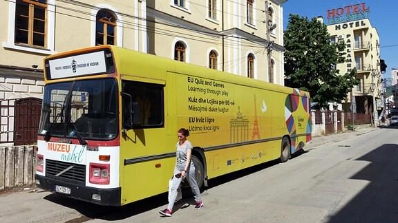 """Frau läuft vor einem gelben Bus durch eine sonnige Straße der kosovarischen Hauptstadt Pristina. Auf dem Bus steht: """"EU-Quiz and Games""""."""