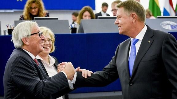 EU-Kommissionschef Jean-Claude Juncker (links) und rumänischer Staatschef Klaus Iohannis begrüßen sich. Hinter Juncker ist die EU-Kommissarin für Regionalpolitik, Corina Cretu, zu sehen.