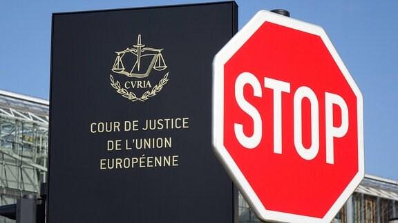 Ein Stopschild steht vor dem Schild des Gerichtshof der Europäischen Union.