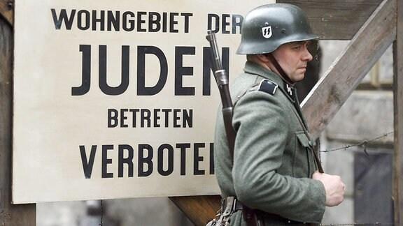 Ein Statist, der ein Mitglied der SS spielt, steht im Filmset vor einem Schild mit der Aufschrift 'Wohngebiet der Juden. Betreten verboten'.