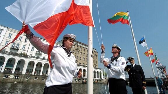 Zwei Matrosen der Deutschen Marine hissen während einer Zeremonie in der Nähe des Hamburger Rathauses die polnische Flagge (l) zur symbolischen Begrüßung der neuen EU-Länder.