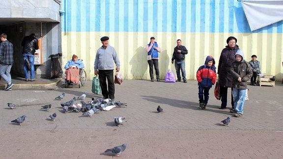 Menschen und Tauben auf einem Platz