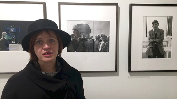 Frau mit Hut vor Fotogalerie