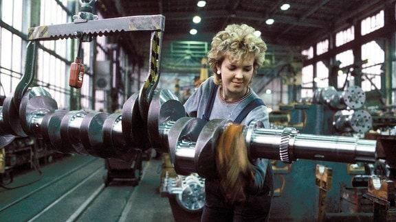 Arbeiterin poliert ein Maschinenteil im VEB -Schwermaschinenbau Karl Liebknecht (SKL) in Magdeburg.
