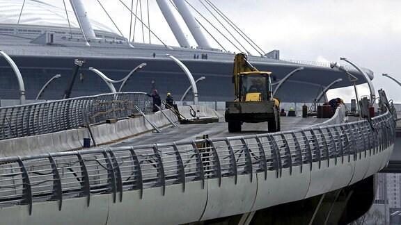 Ein Bagger fährt über die noch im Bau befindliche Zubringerbrücke zum Stadion in St. Petersburg.